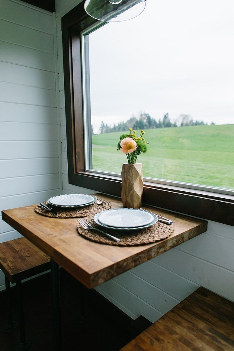 Small and beautiful dining area next to the window with wooden seats for two