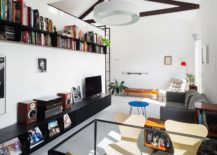 Small-space-savvy-apartment-has-a-living-room-with-bookshelf-that-is-placed-above-entertainment-unit-217x155