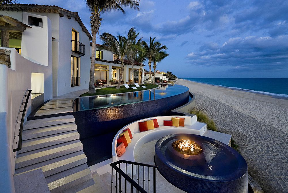 Tropical pool with fire pit at its heart next to the beach and sunken seating