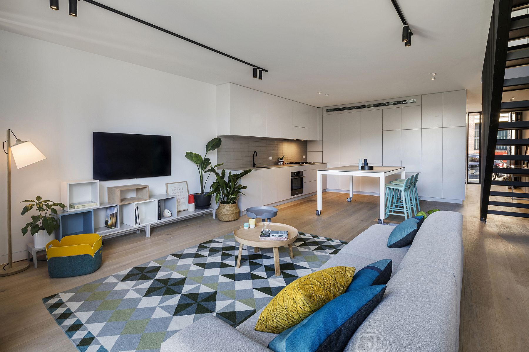 White living area with blue and yellow accents and a striking rug
