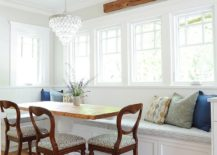 Accent-pillows-wooden-trims-and-dining-chairs-add-contrast-to-the-white-dining-room-backdrop-217x155