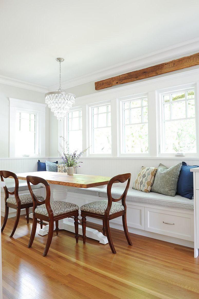 Accent pillows, wooden trims and dining chairs add contrast to the white dining room backdrop
