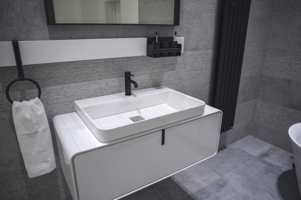 Bathroom with stone-like wall tiles and contrasting white vanity