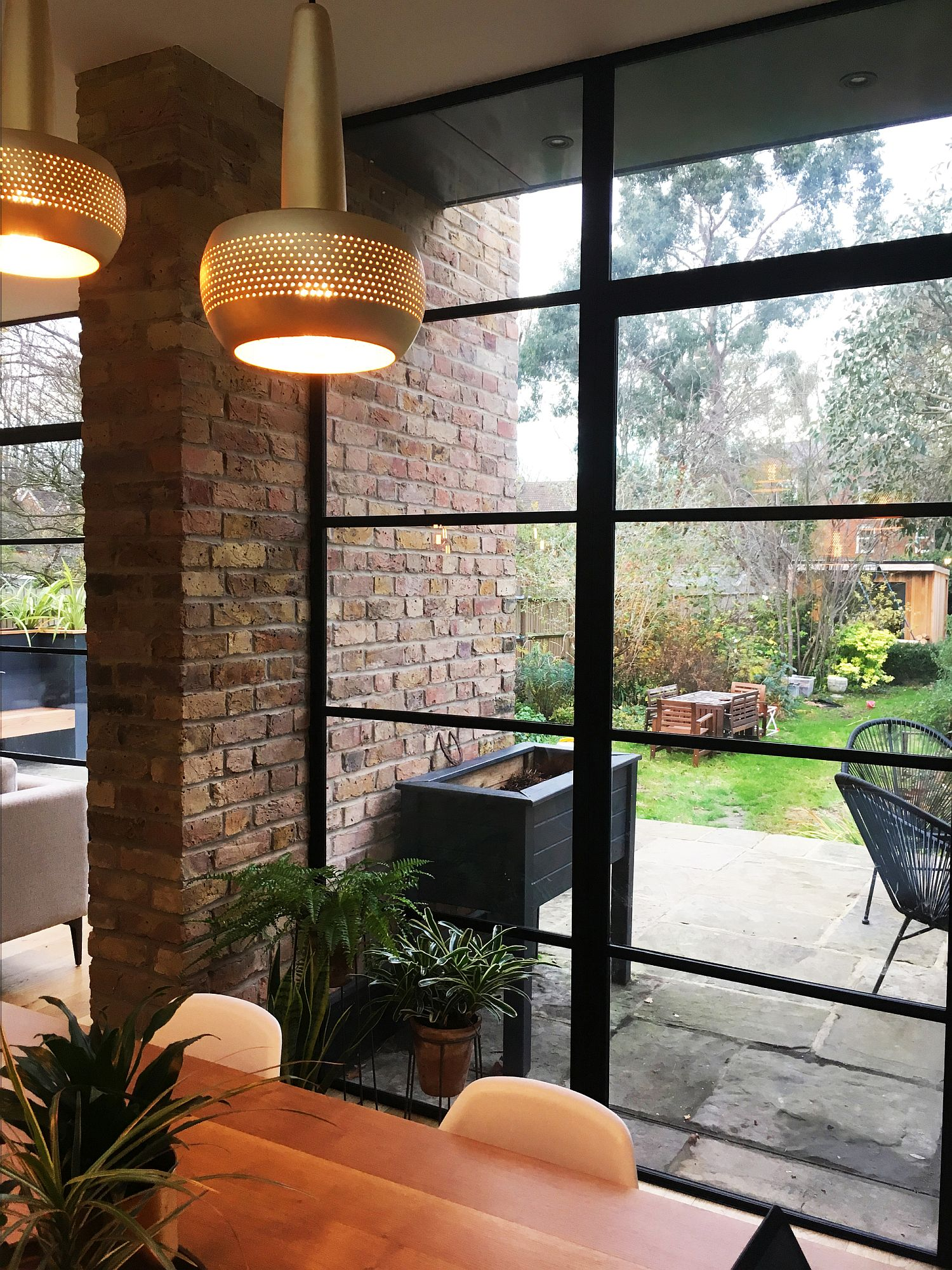 Brick walls coupled with framed glass windows inside the house