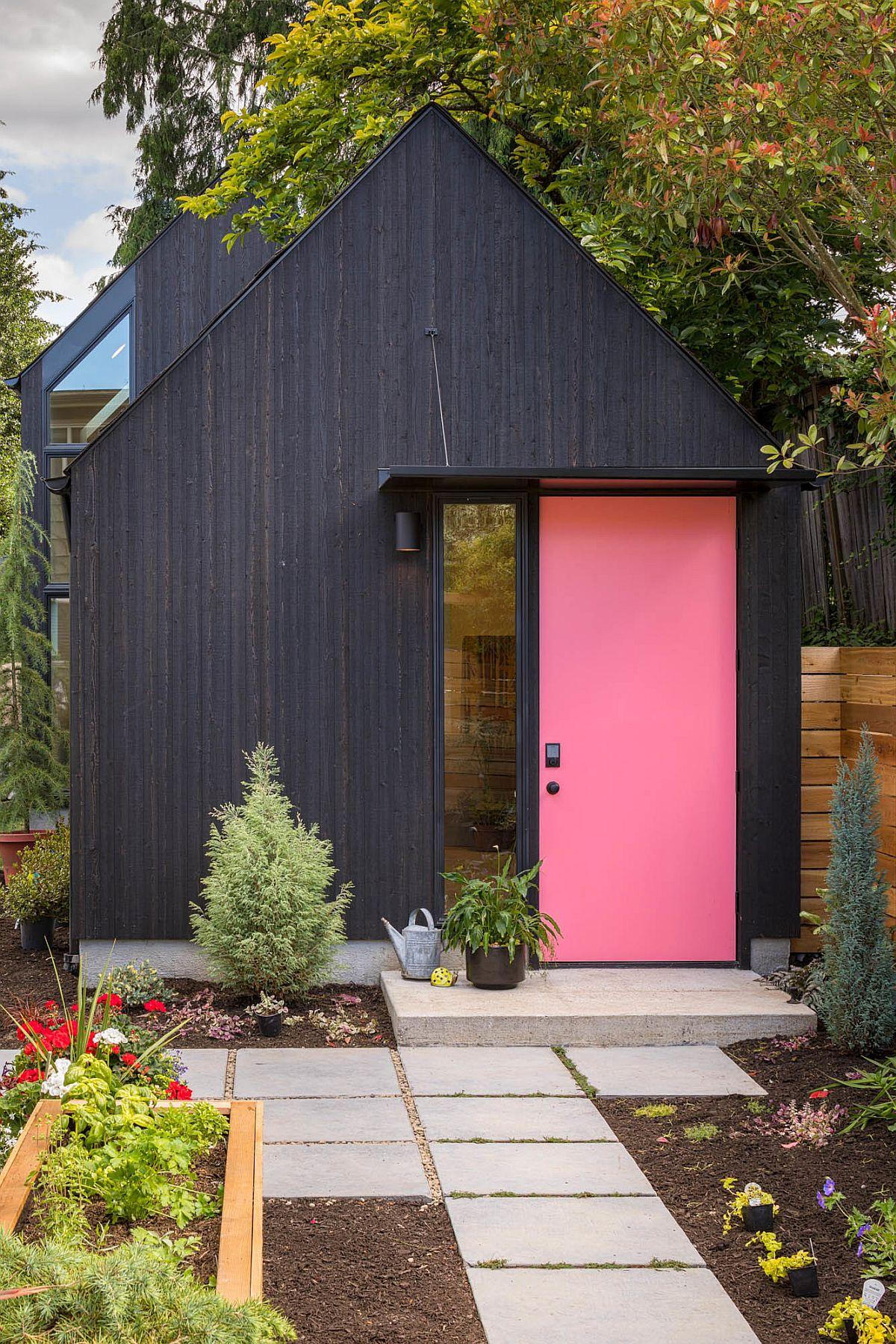 Dark exterior of the home with pink door