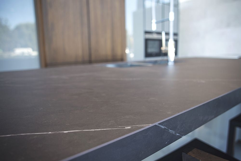 Dark kitchen island countertop with glossy grey cabinets – Porcelanosa