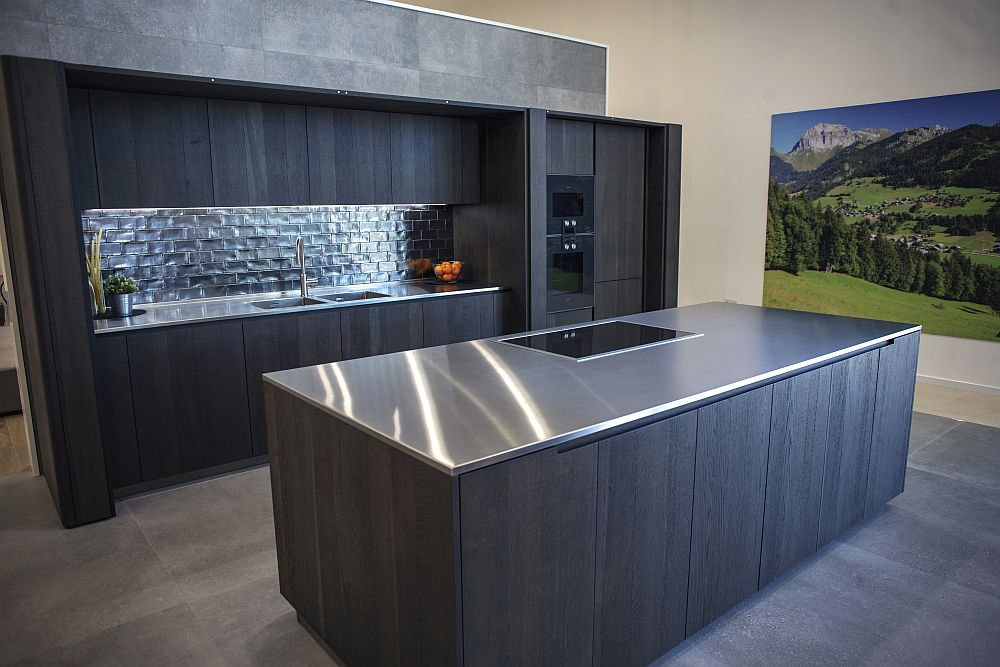 Dark themed large kitchen design with stainless-steel countertops