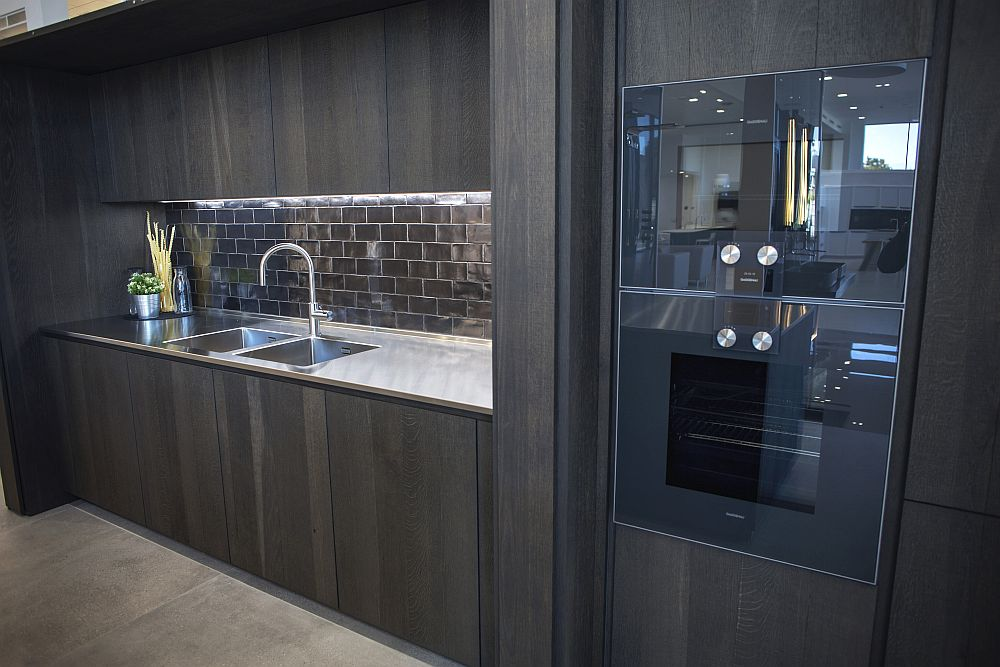 Dark wood kitchen with glossy subway tiles backsplash and under-cabinet lighting