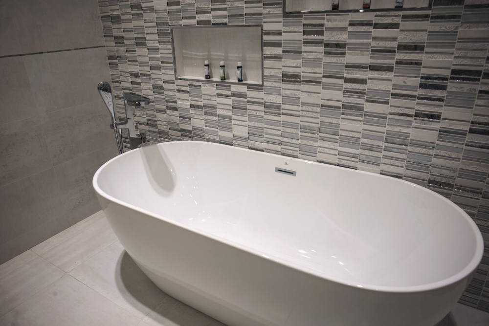 Free-standing bathtub with glossy tiles backdrop – Porcelanosa