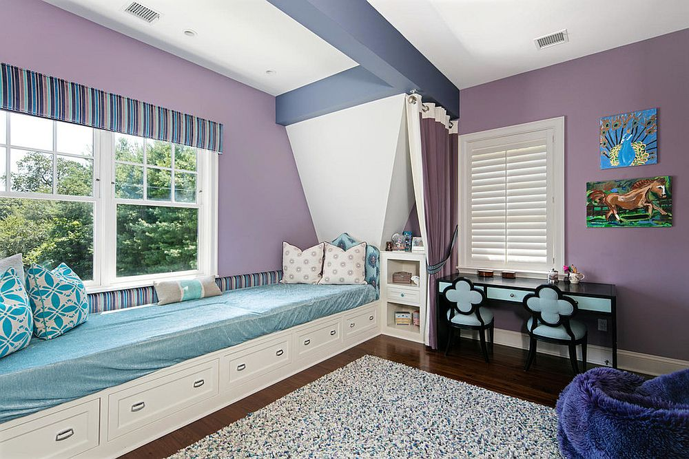 Girls' bedroom in purple with a plush window seat that has built-in storage