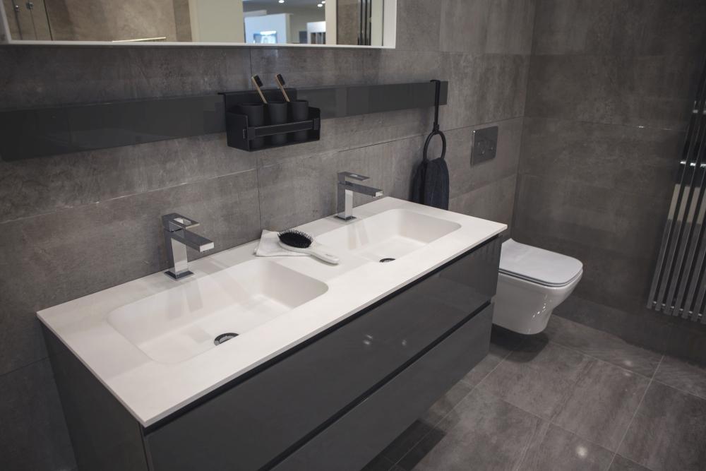 Grey modern bathroom with white wash basins for contrast