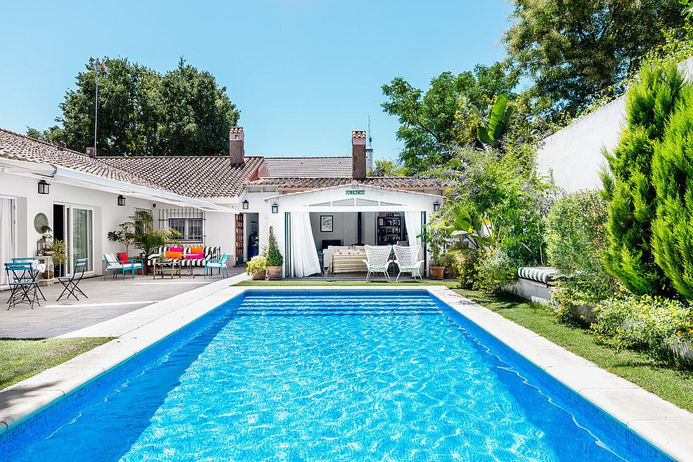 Mediterranean pool house in white with terra cotta tiles brings home the holidays