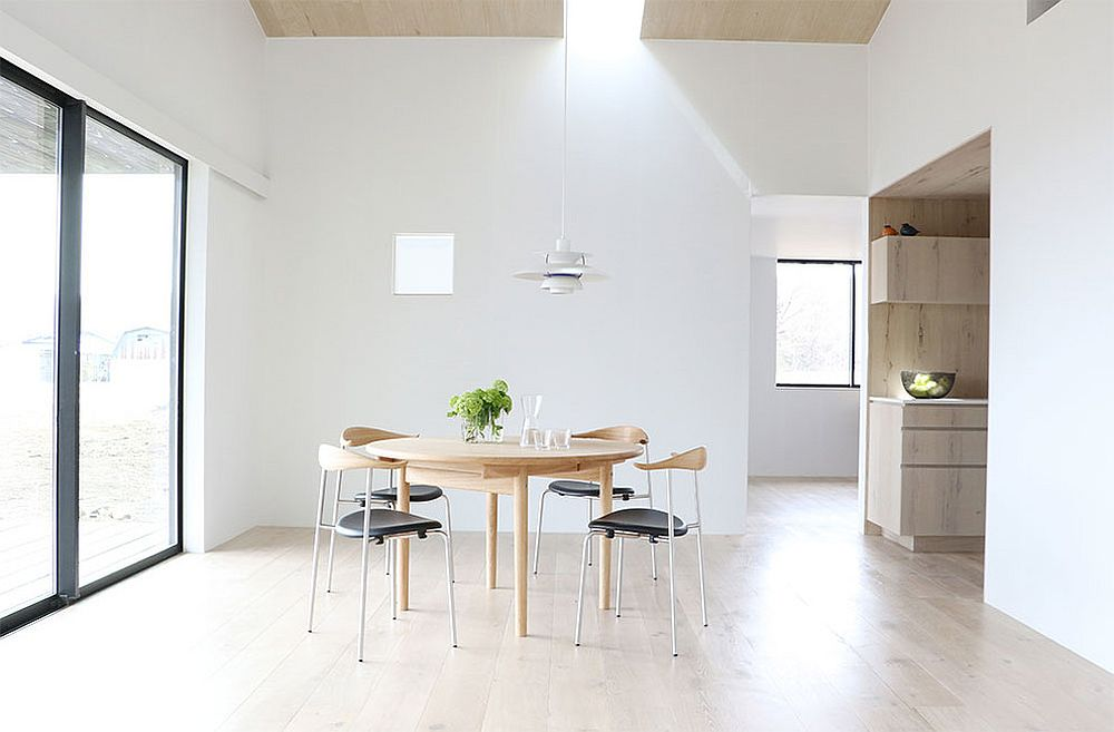 Minimal dining room in white and wood with skylight
