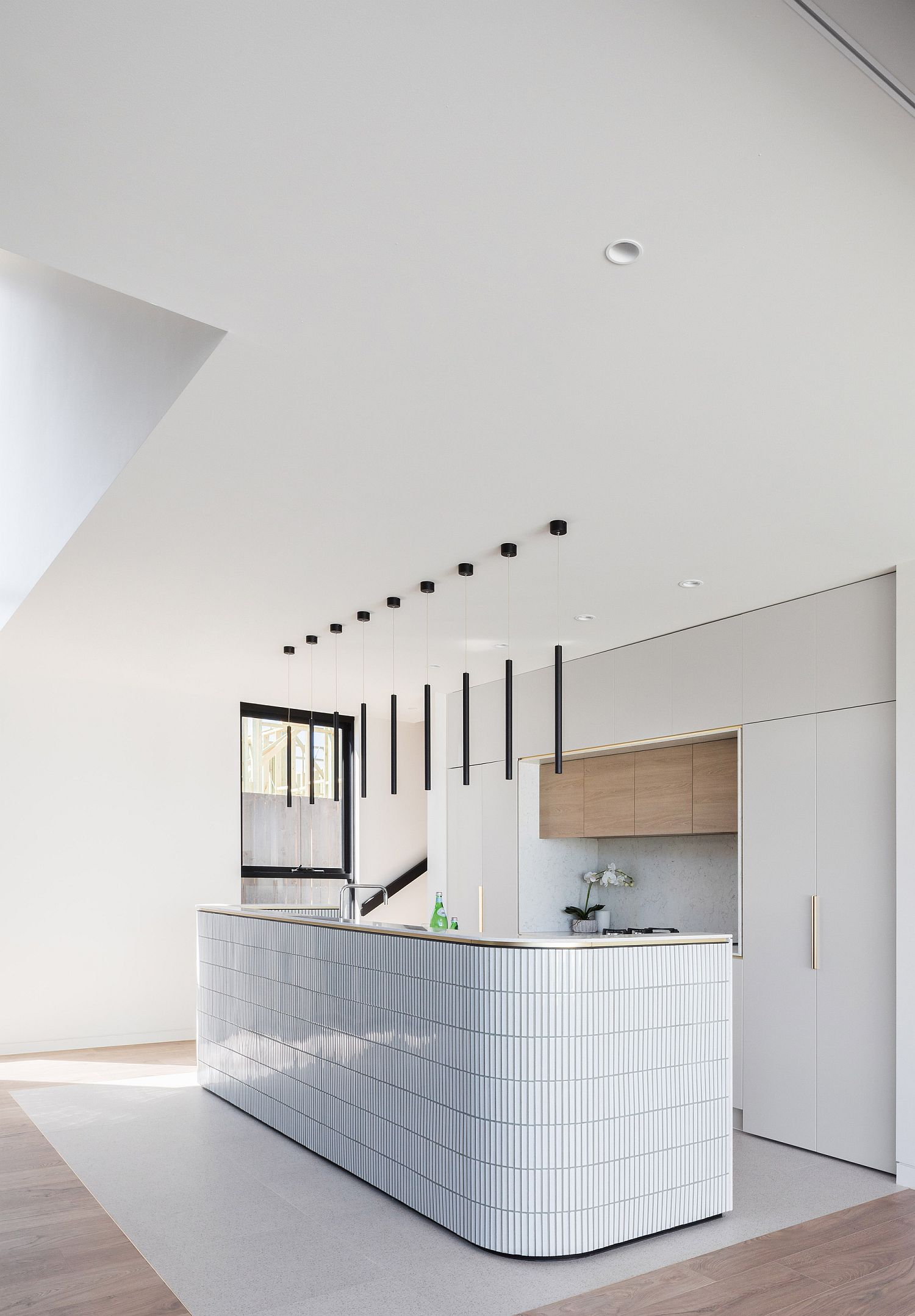 Minimal kitchen with curved island that is a showstopper