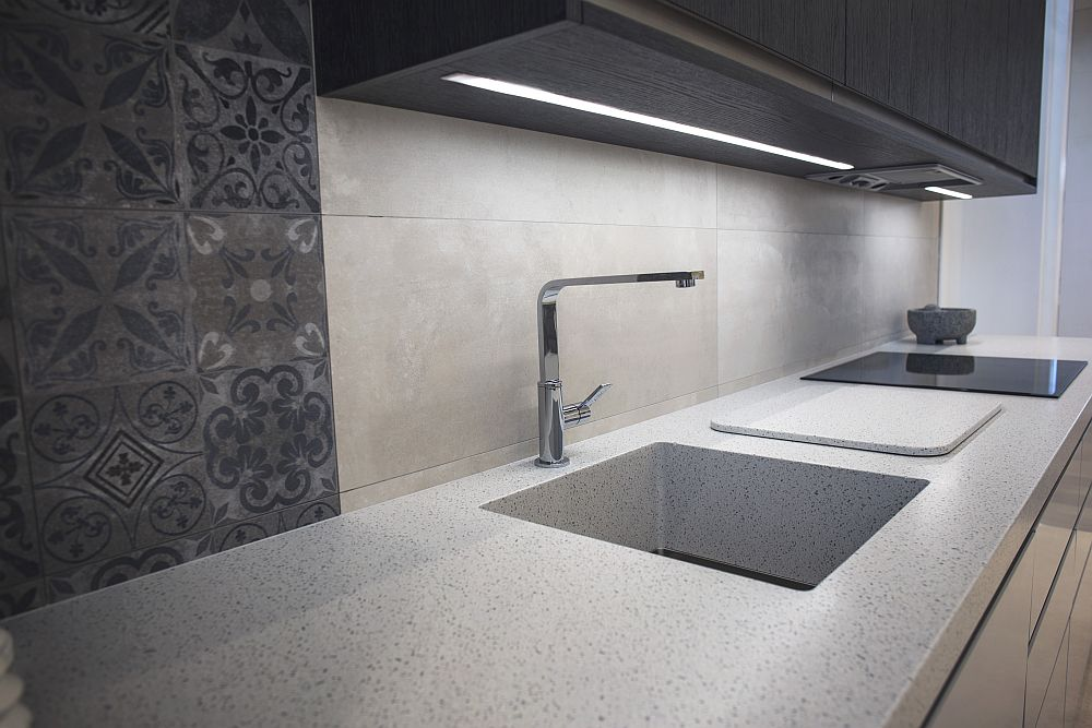 Modern kitchen countertop with under-cabinet LED lights by Porcelanosa