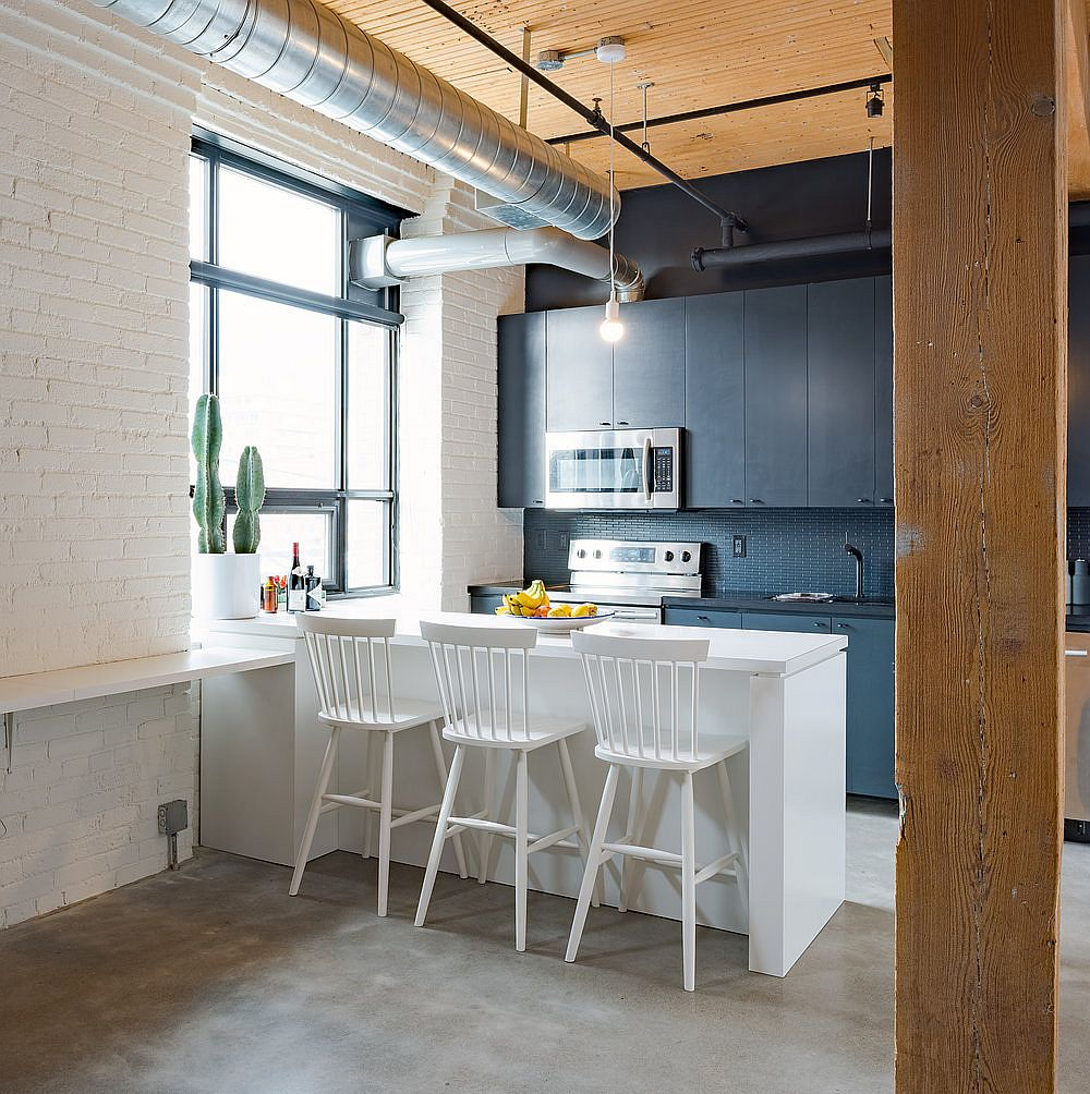Painted brick wall in white along with wood and grayish-blue kitchen section for the small loft