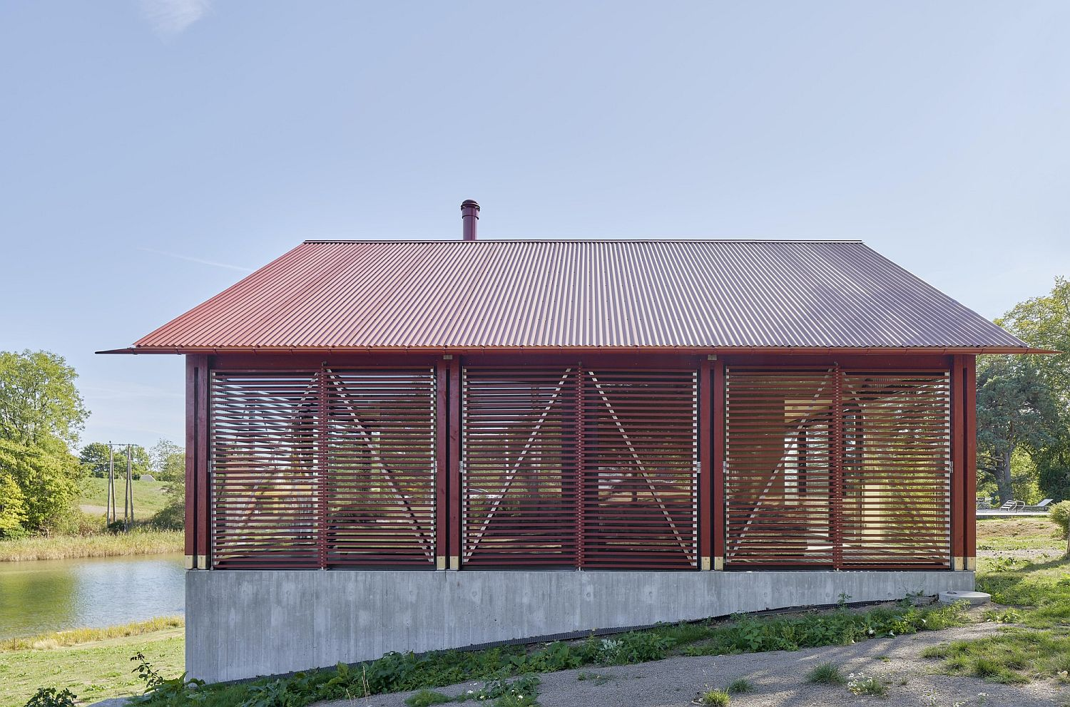 Wooden shutters and glass create the outer shell of the pavilion style cabin