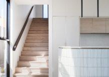 Wooden-stairway-next-to-the-curved-kitchen-island-217x155