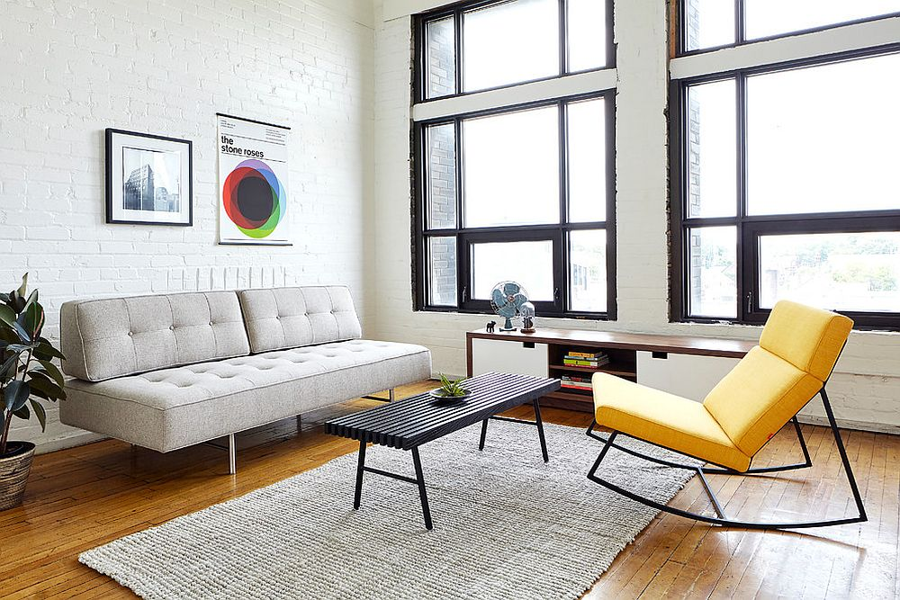Yellow recliner coupled with light gray sofa and white brick wall backdrop in the living space