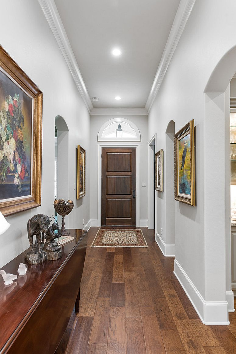 Art gallery-style entry in white with framed art work on the walls