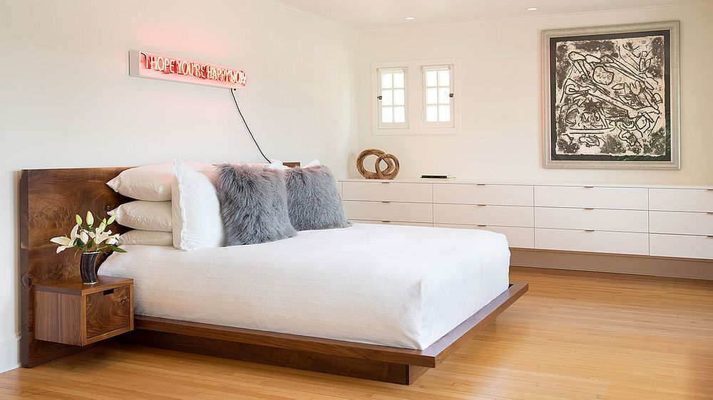 Contemporary bedroom in white with an illuminated neon sign above the headboard