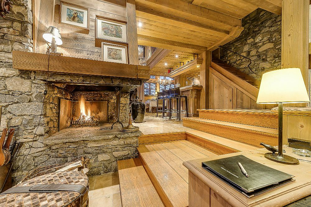 Cozy stone fireplace in the large living area that can accomodate 15 guests with ease