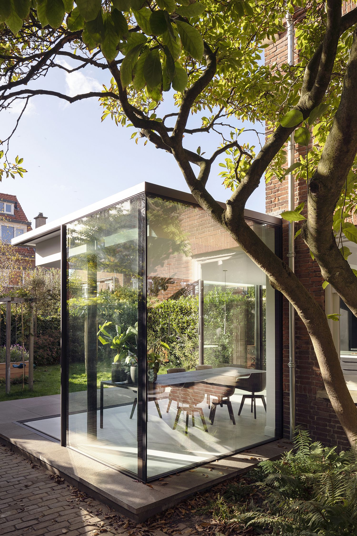 Glass walled extension of the traditional brick house in Netherlands