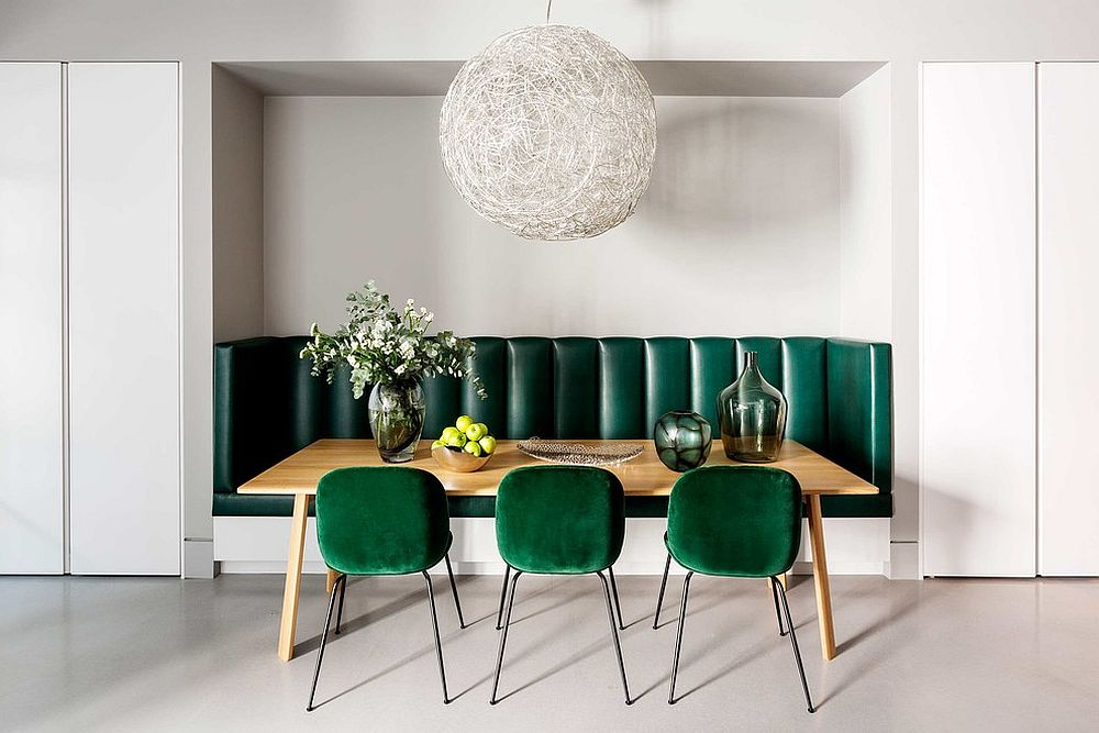 Gorgeous use of dark green chairs and banquette seating in the white dining room with Moooi Random Light
