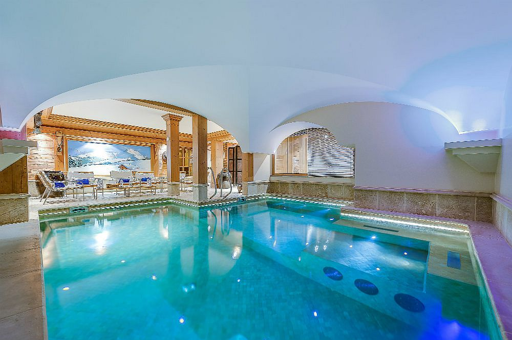 Indoor heated pool with water jets and a private spa next to it
