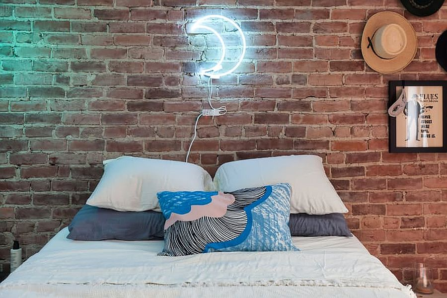 Industrial chic bedroom with brick wall and neon light shaped like the moon!