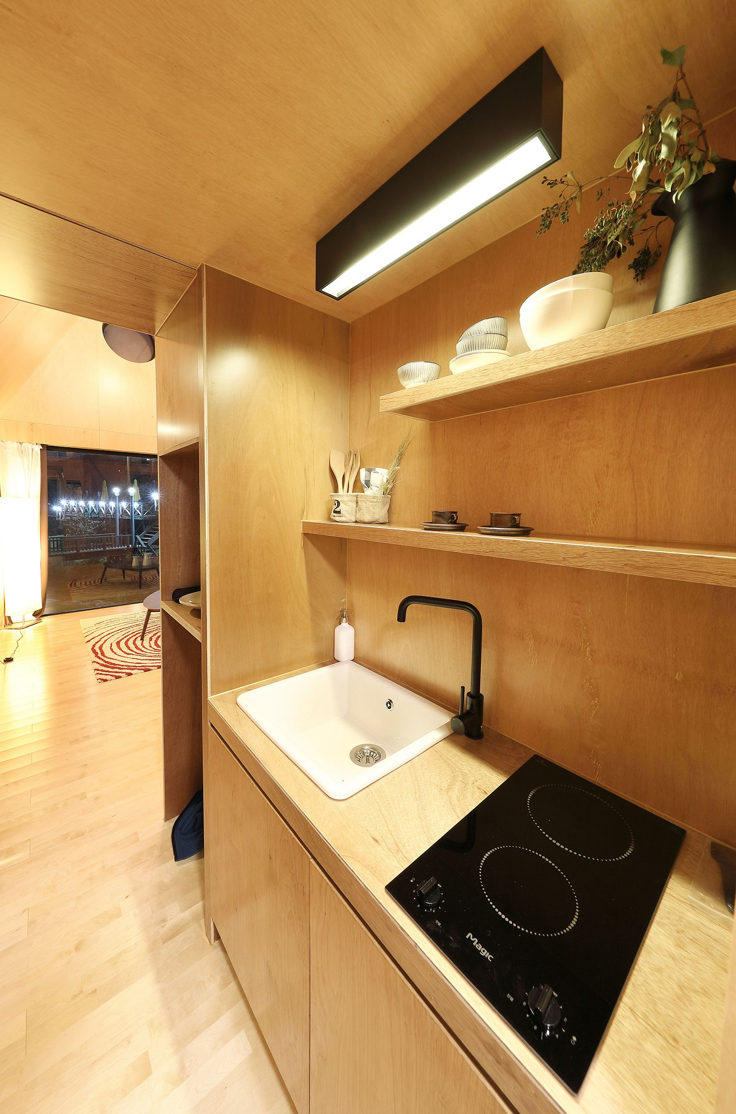 Kitchen of the tiny house with wooden shelves and smart cabinets