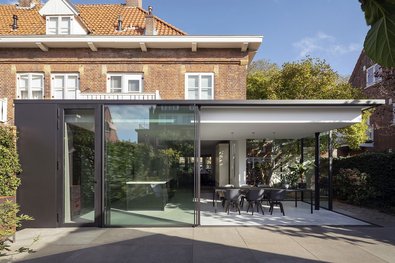 Old brick house in Netherlands with modern glass and concrete extension