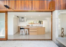 Sliding-glass-walls-with-wooden-frame-for-the-modern-kitchen-in-white-217x155