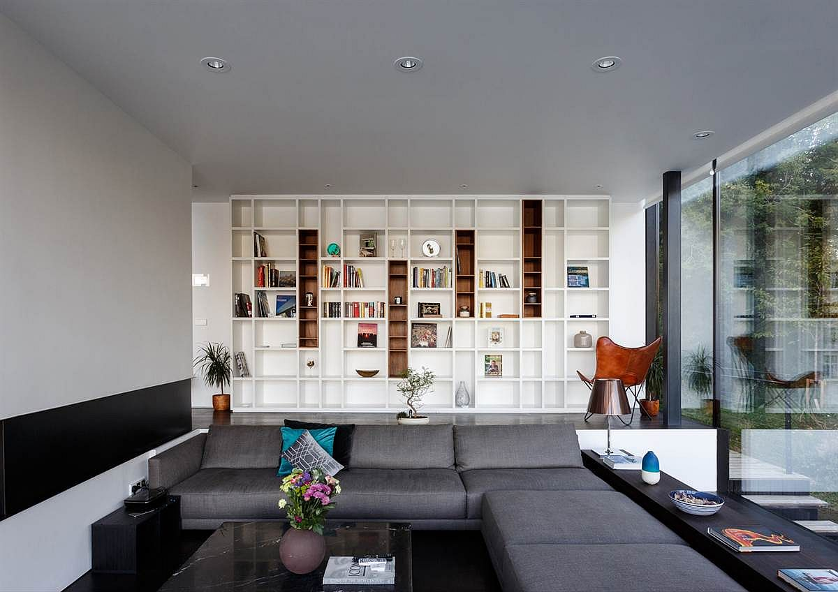 Sunken living room with large gray sectional and white bookshelf in the backdrop