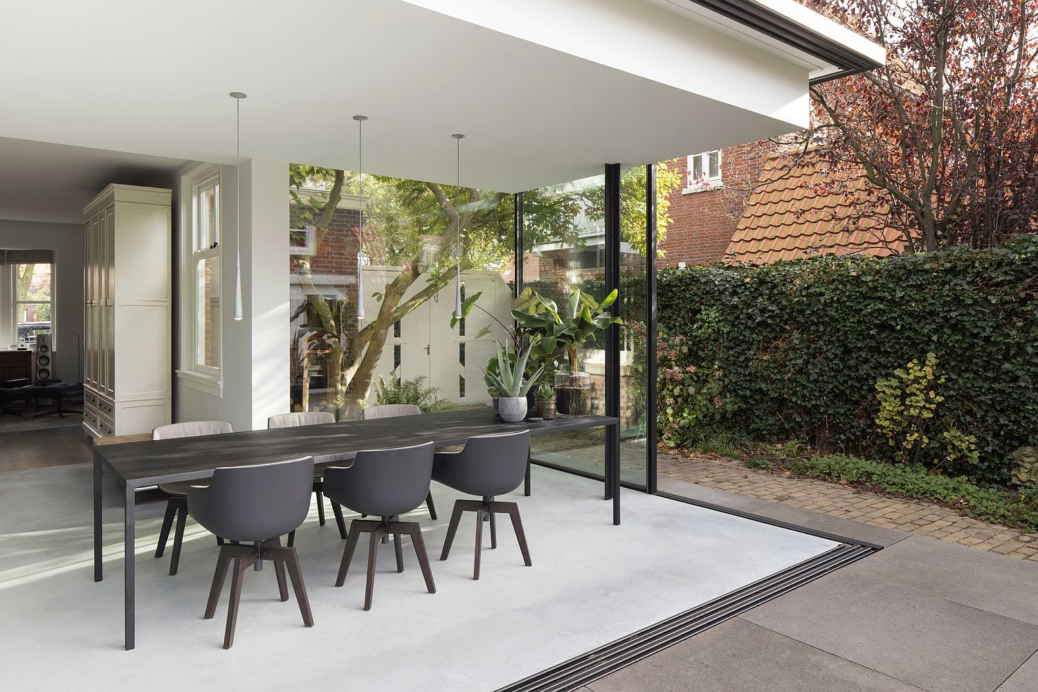 White and gray dining room connected with the Fig Tree landscape outside