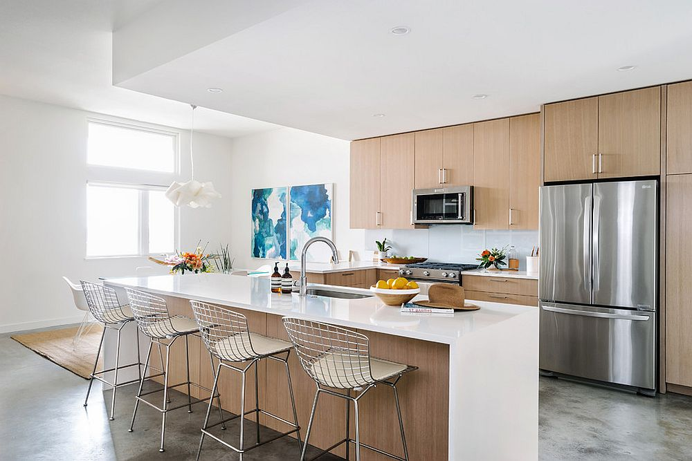 White and wood beach style kitchen with blue wall art in the corner