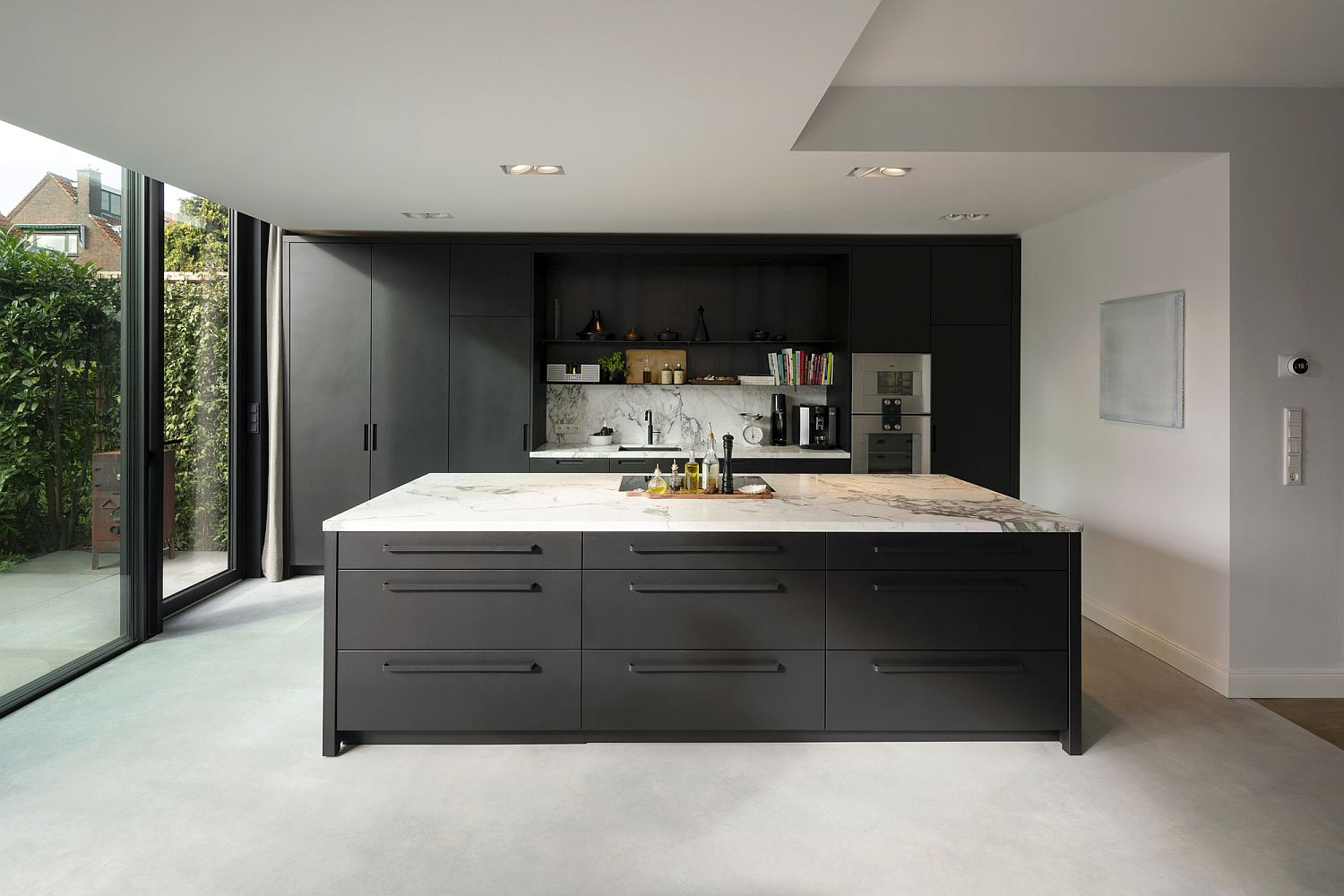 White kitchen with marble countertops and dark island along with dark gray shelving