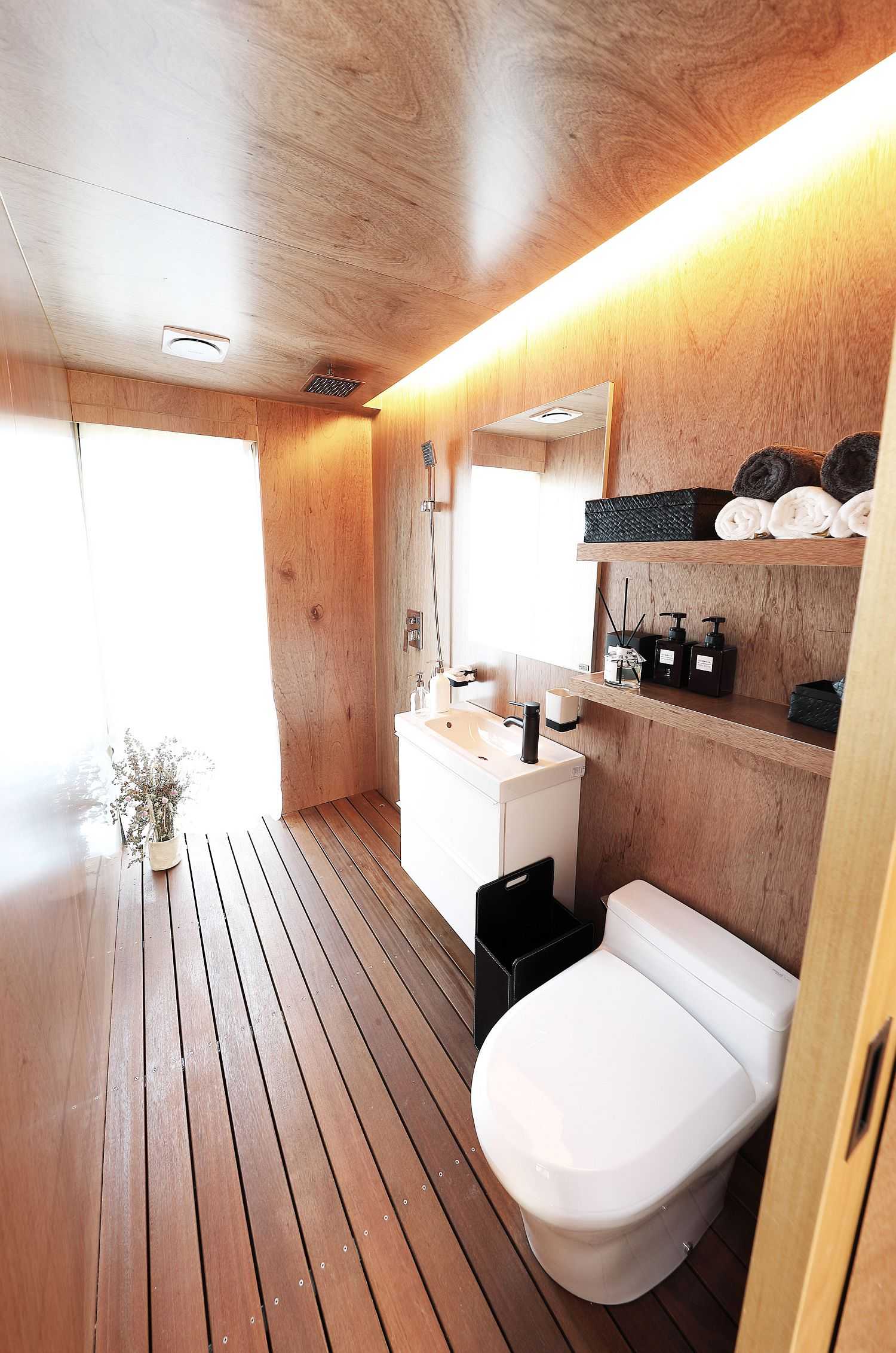 Wood bathroom with a pinch of white brought in by toilet fixtures