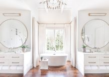 Wooden-floor-brings-warmth-to-the-all-white-bathroom-with-metallic-accents-217x155