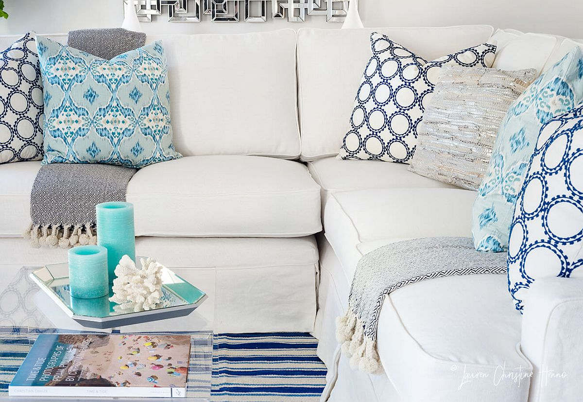 Accent pillows and decor bring blue to the white living room