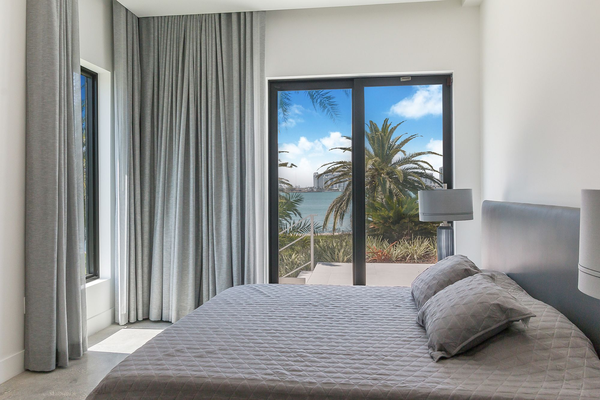 Beach style bedroom in white and gray with a view to match