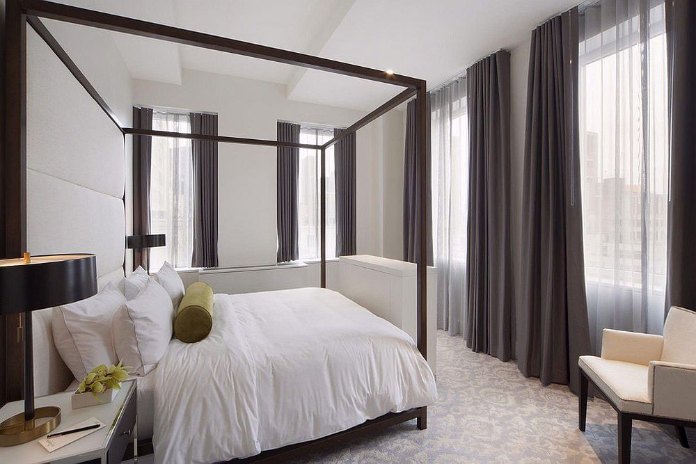 Bedroom in white with dark gray drapes