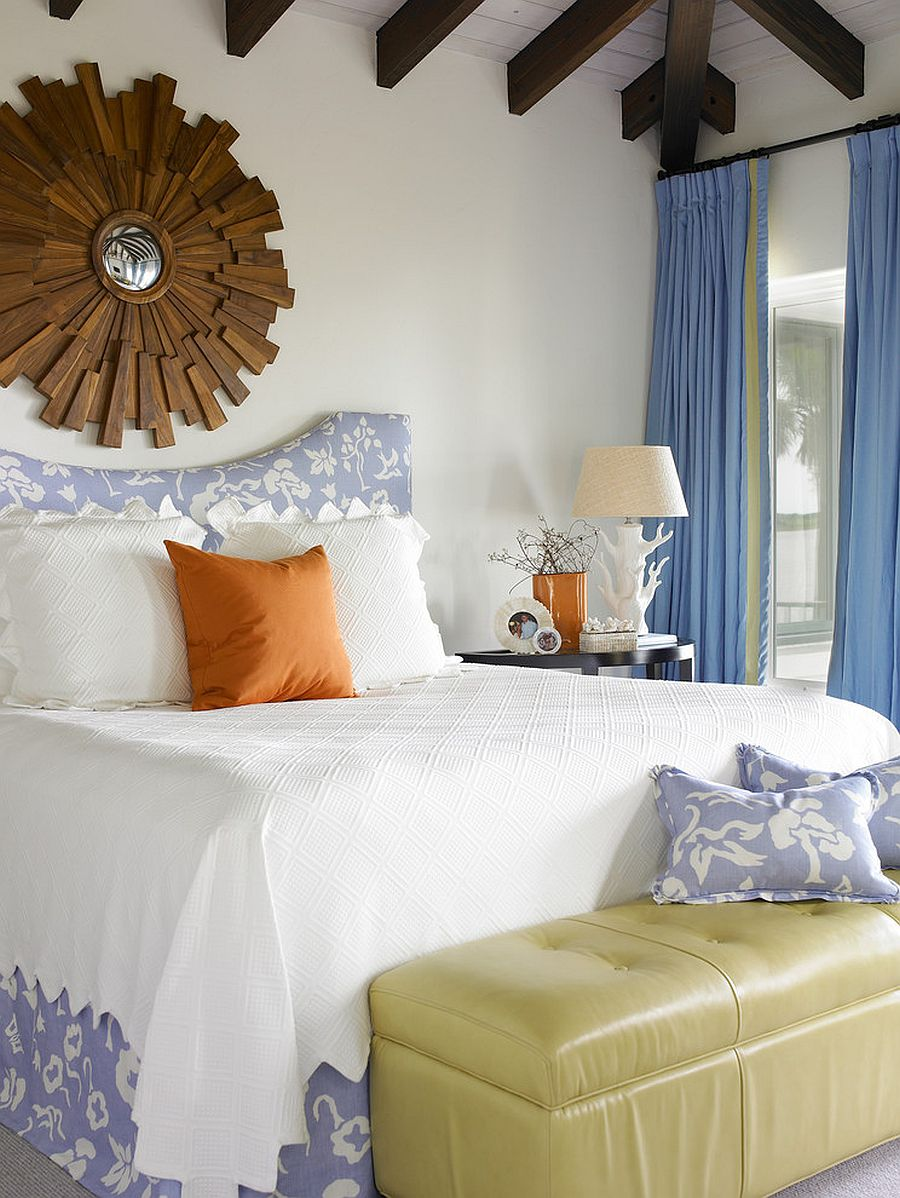 Blue drapes add to the appeal of the spacious beach style bedroom