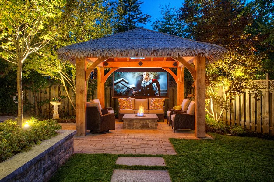Bring the exotic tropical resort vibe to the backyard with a cool hut and outdoor home theater