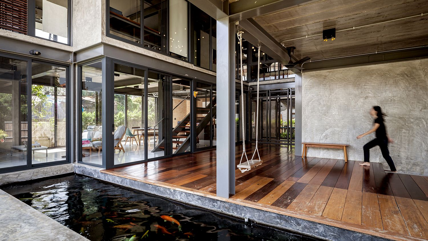 Glass walls, curated natural landscape and koi pond bring serenity to this spacious Bangkok home