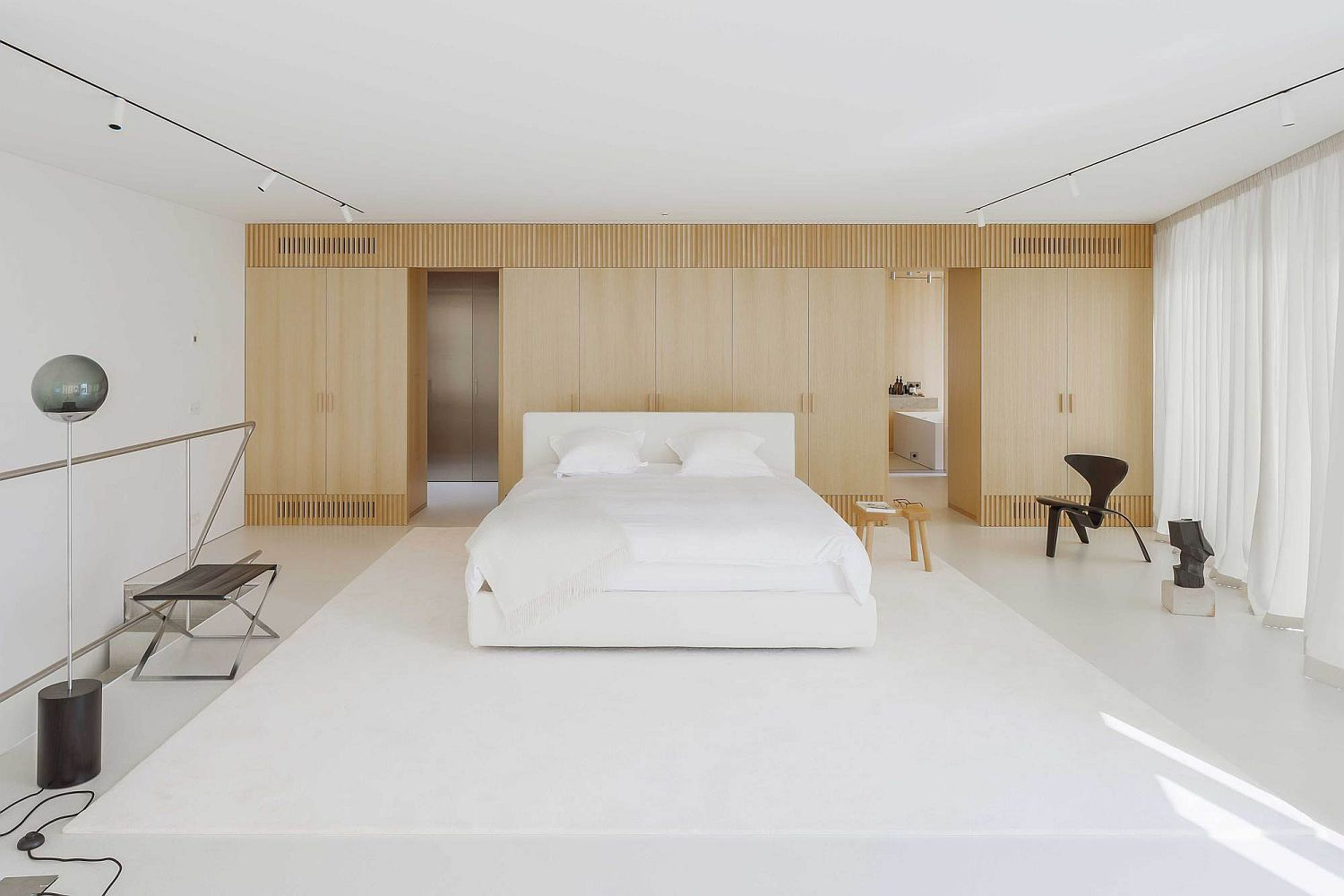 Minimal bedroom in white with wooden accent wall