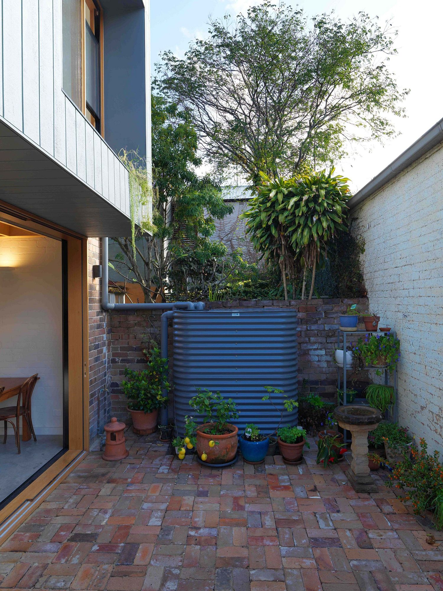 Overhang created by the rear second-level additions provides shade to the tiny backyard