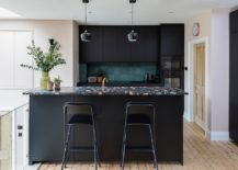 Stylish-Scandinavian-kitchen-in-black-with-a-colorful-countertop-and-a-dark-green-backsplash-217x155