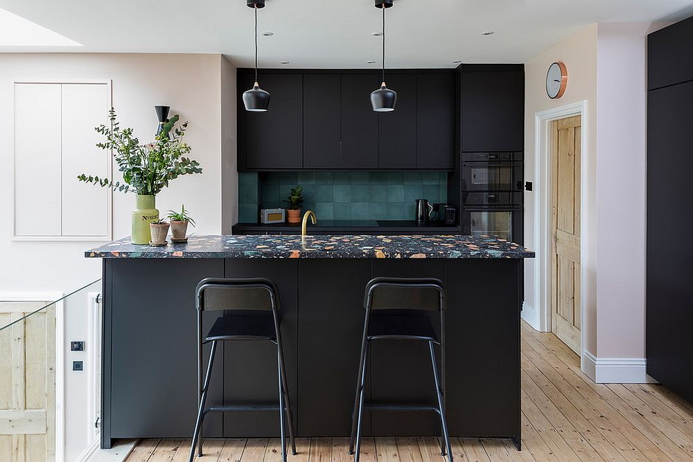 Stylish Scandinavian kitchen in black with a colorful countertop and a dark green backsplash