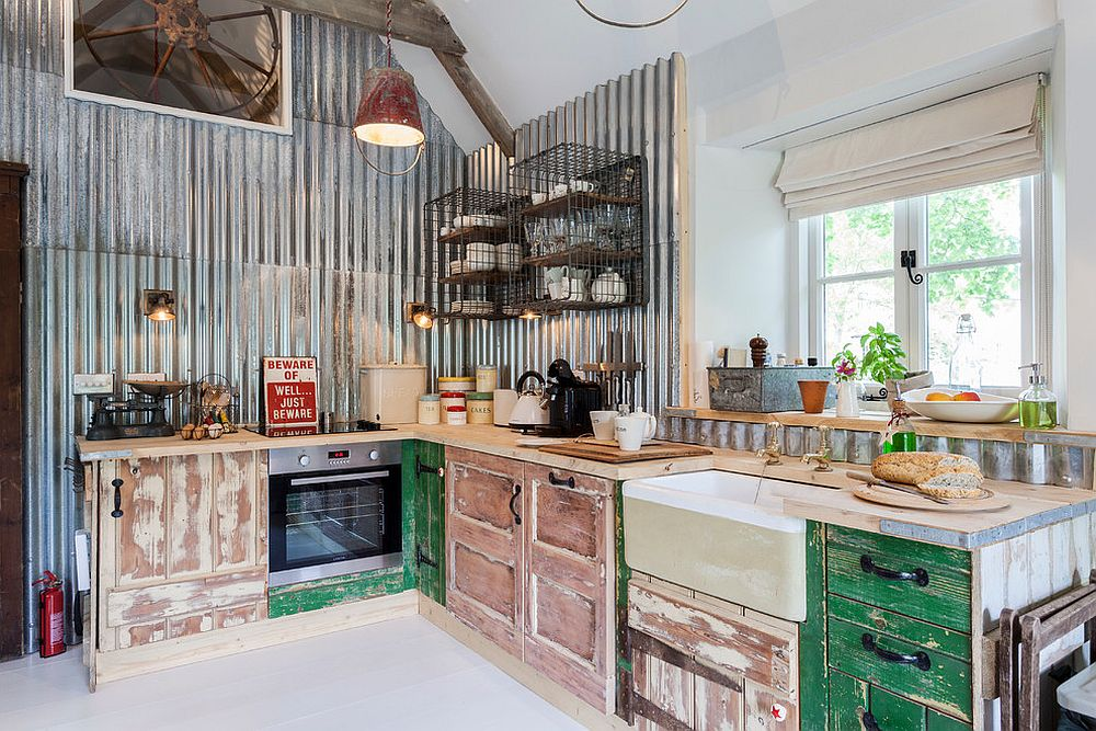 Unique kitchen with weathered wooden cabinets and metallic backdrop
